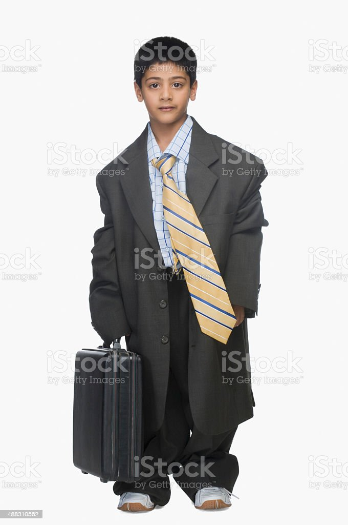 Portrait of a boy wearing oversized suit and holding briefcase stock photo