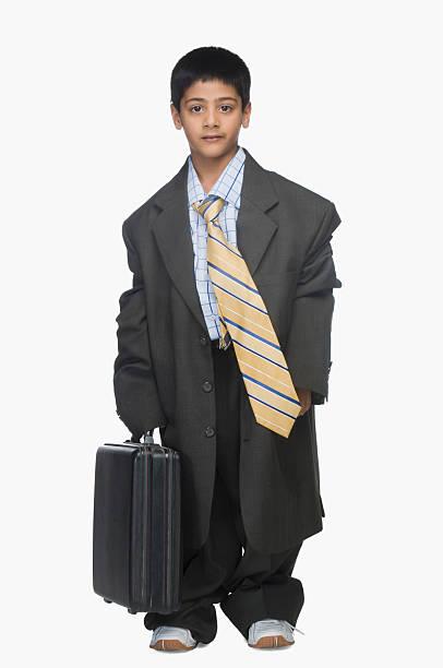 portrait of a boy wearing oversized suit and holding briefcase - te groot stockfoto's en -beelden