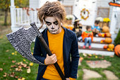 Close up portrait of a boy with  zombie make-up and a Halloween axe. His friends sitting on the steps in the background.