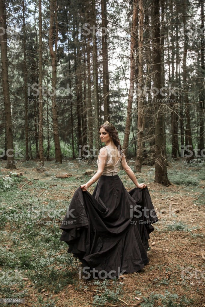 portrait of a bride dressed in non traditional wedding dress outdoors in the woods stock photo