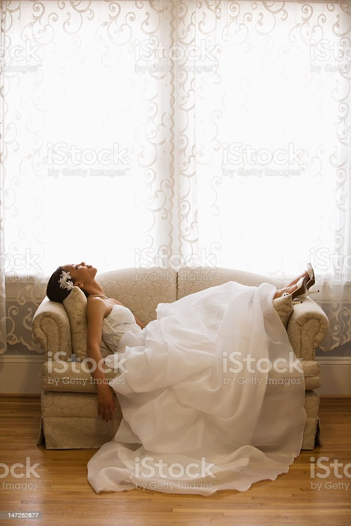 A portrait of a bride laying on a couch stock photo