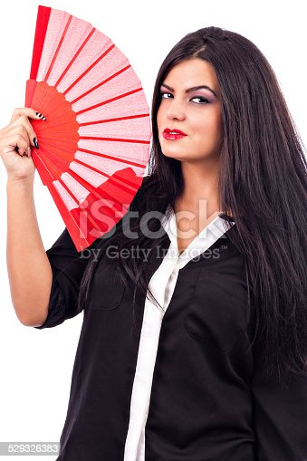 istock Portrait of a brunette young woman holding red fan 529326383