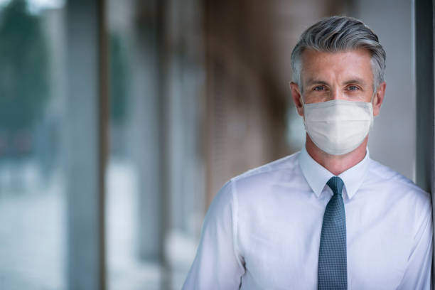 portrait of a business man wearing a facemask at the office - businessman covid mask foto e immagini stock