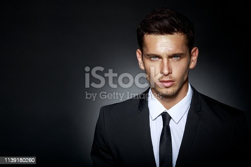 Close up of a attractive brunette young man model, posing in posture of a businessman, wearing a classical black suit, isolated on black background. Vertical view.