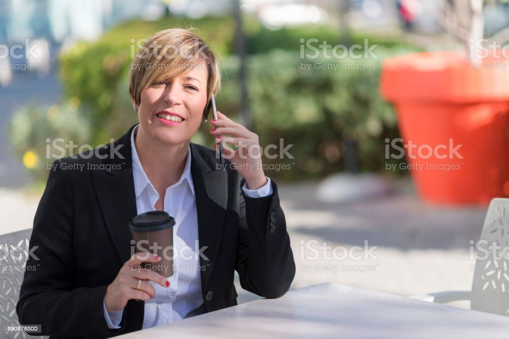 Portrait of a business woman sitting relaxed at outdoor cafe stock photo