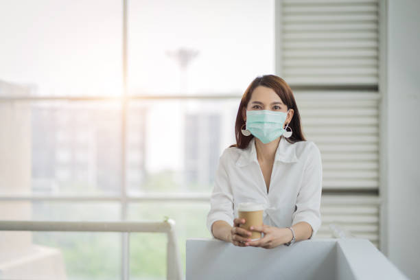 Portrait of a business woman with business suit wears face mask holds morning coffee cup in company building ready for work. A middle age woman with face mask to protect COVID-19 pandemic. stock photo stock photo