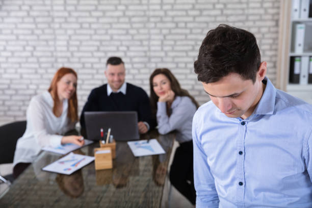 Portrait Of A Businessman In Office Portrait Of A Businessman With His Colleagues In Background At Office harassment stock pictures, royalty-free photos & images