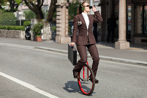 Portrait of a businessman on a unicycle drinking coffee