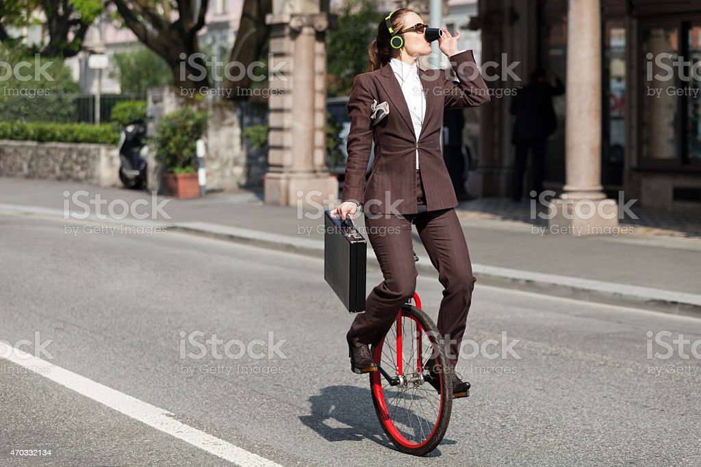Portrait of a businessman on a unicycle drinking coffee stock photo