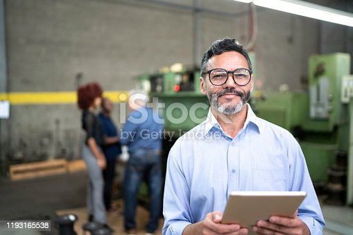 Portrait of a businessman using a digital tablet in the production line of a factory