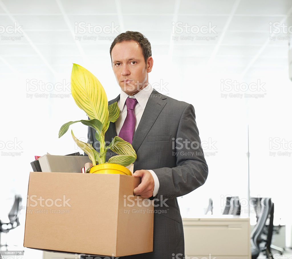Portrait of a businessman with cardboard box of office items