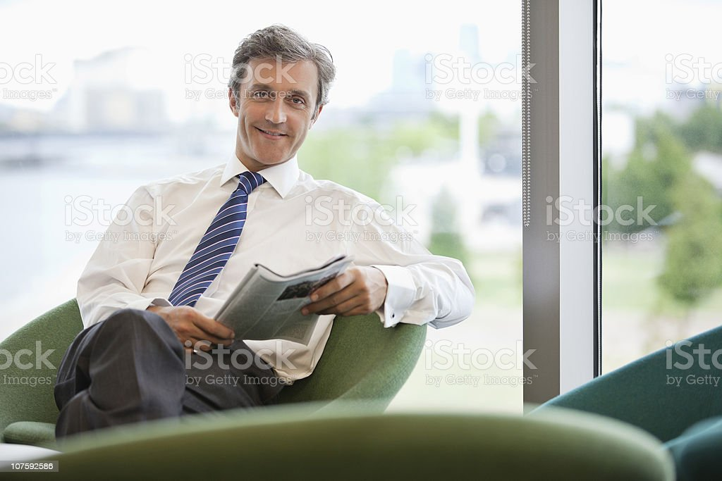 Portrait of a businessman with magazine sitting at office cafeteria royalty-free stock photo
