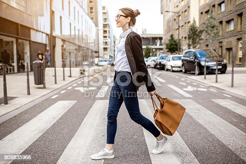 Young businesswoman crossing the street at the modern office district in Lyon city