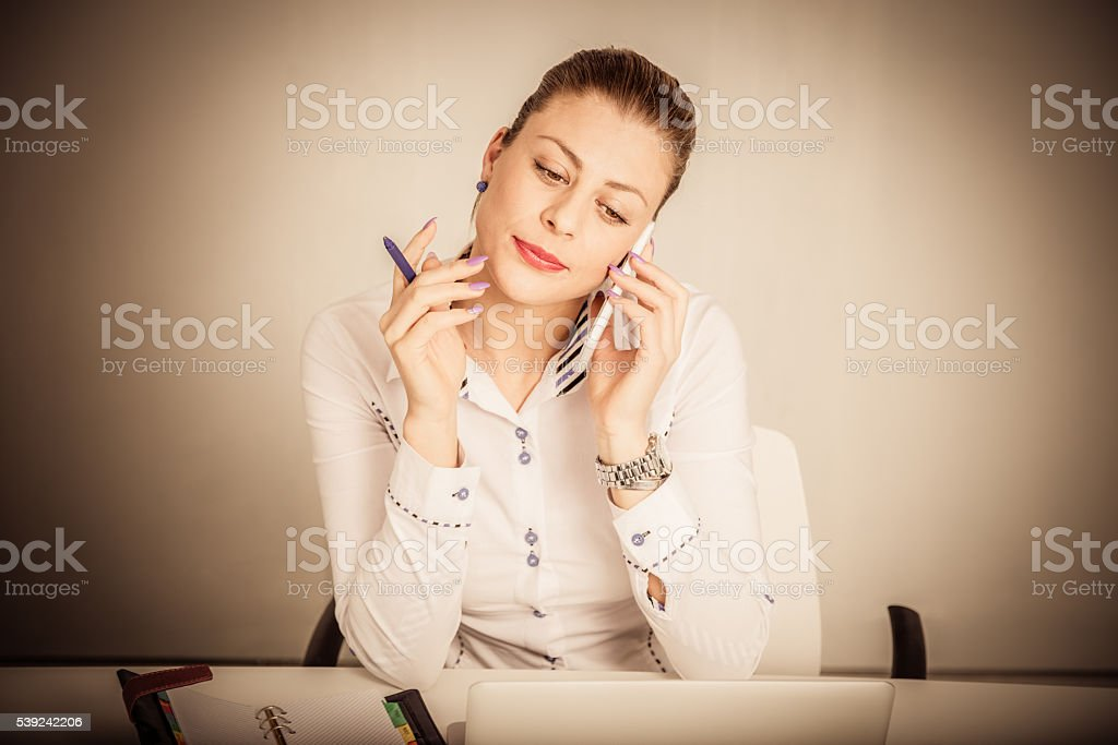Portrait of a businesswoman using smartphone at the desk royalty-free stock photo