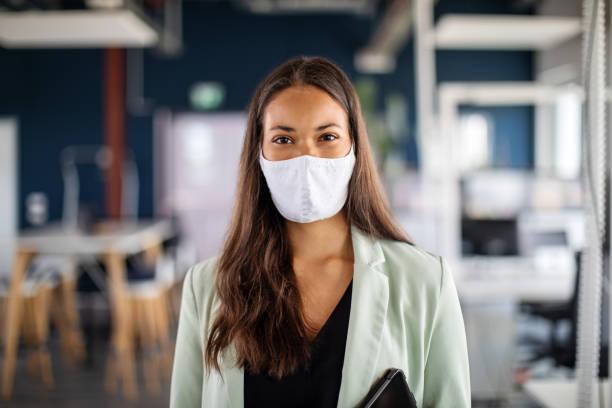 porträt einer geschäftsfrau mit gesichtsmaske im büro - alvarez stock-fotos und bilder