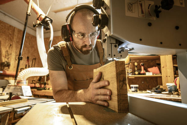 portrait of a carpenter inside his carpentry workshop using a band saw. portrait of a carpenter inside his carpentry workshop using a band saw. Wear ear and eye protection carving craft activity stock pictures, royalty-free photos & images
