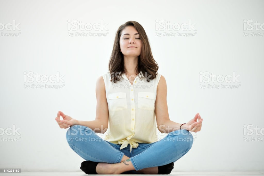 Portrait of a casual pretty woman meditating on the floor on white background stock photo
