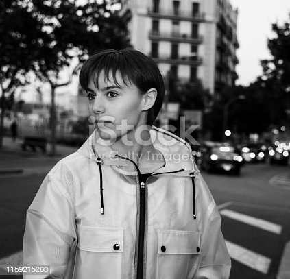 Portrait of a casual young girl wearing a translucent raincoat in Barcelona streets. Black and White.