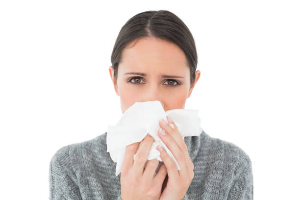 Portrait of a casual young woman suffering from cold Closeup portrait of a casual young woman suffering from cold over white background human parainfluenza virus stock pictures, royalty-free photos & images