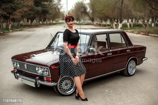 portrait of a Caucasian beautiful young girl in a black vintage dress, posing near a vintage car