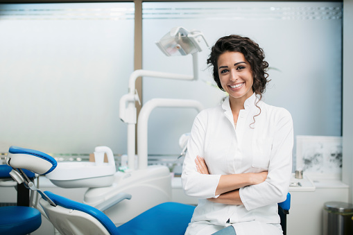 Portrait of a Caucasian woman dentist, sitting in her office next to a dentist chair, smiling