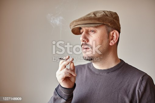 Portrait of a caucasian man with a hat taking a smoke from his cigarette