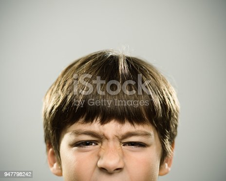 Close up half face portrait of frowning caucasian real kid looking at camera. The boy is 7 years old and has brown hair. Horizontal shot of little boy making a face against white background. Photography from a DSLR camera. Sharp focus on eyes.