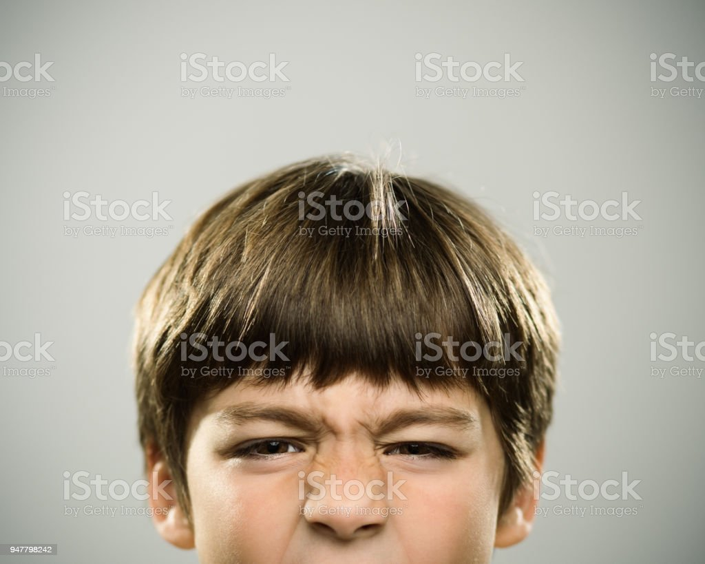 Portrait of a caucasian real boy frowning. stock photo