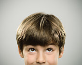 Close up half face portrait of a happy caucasian real kid looking up. The boy is 7 years old and has brown hair. Horizontal shot of little boy looking around against white background. Photography from a DSLR camera. Sharp focus on eyes.