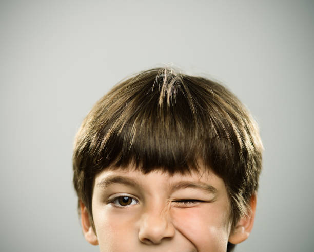 Portrait of a caucasian real boy winking. Close up half face portrait of playful caucasian real kid looking at camera. The boy is 7 years old and has brown hair. Horizontal shot of little boy winking the eye against gray background. Photography from a DSLR camera. Sharp focus on eyes. blinking stock pictures, royalty-free photos & images