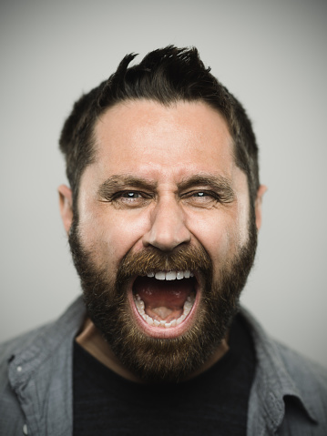 Portrait of a real caucasian young man with screaming with excited expression looking at camera. Brown eyes and hair with beard. 35 years old north american. Vertical color image from a dslr camera in studio.