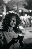 Portrait of a caucasian young adult woman holding sparklers
