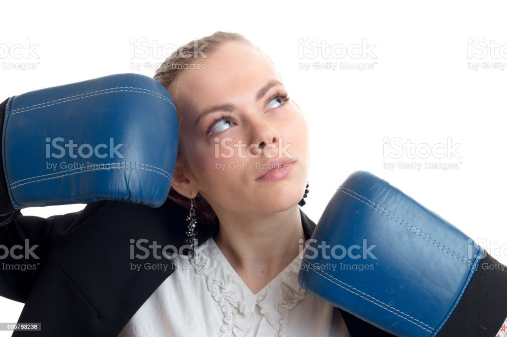 Portrait of a charming blonde that looks up and keeps hands near the person in blue boxing gloves royalty-free stock photo