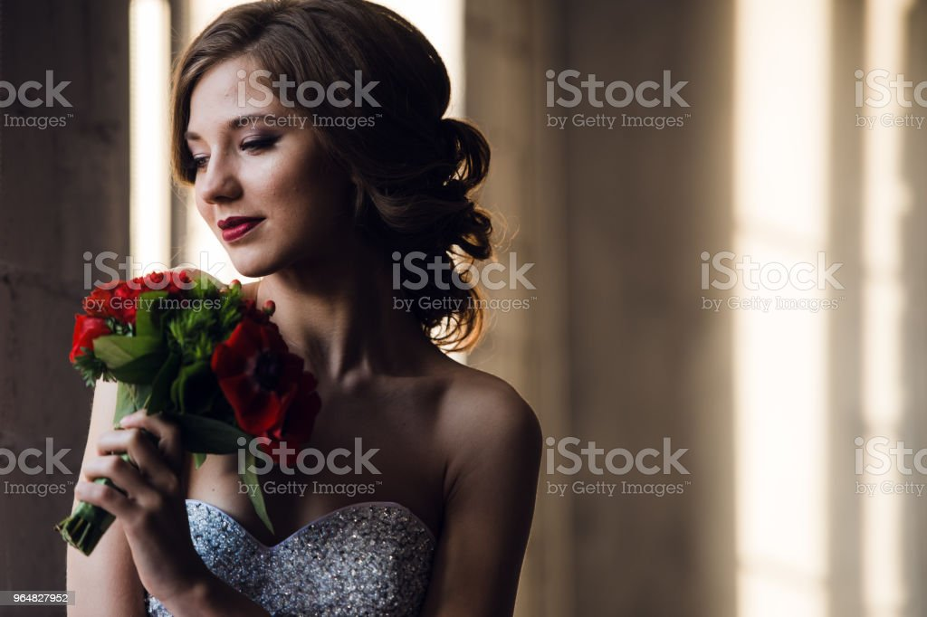 Portrait of a charming girl with beautiful smile and red lipstick, looking up, with a bouquet of red roses on the background of the interior, close-up royalty-free stock photo