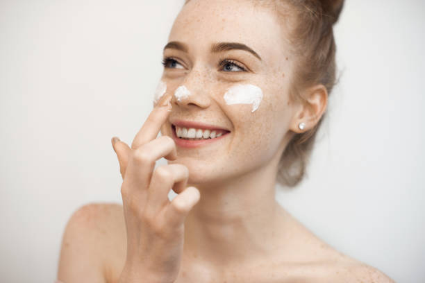 Portrait of a charming young female with red hair and freckles isolated on white applying a anti age cream on her face and nose smiling. stock photo