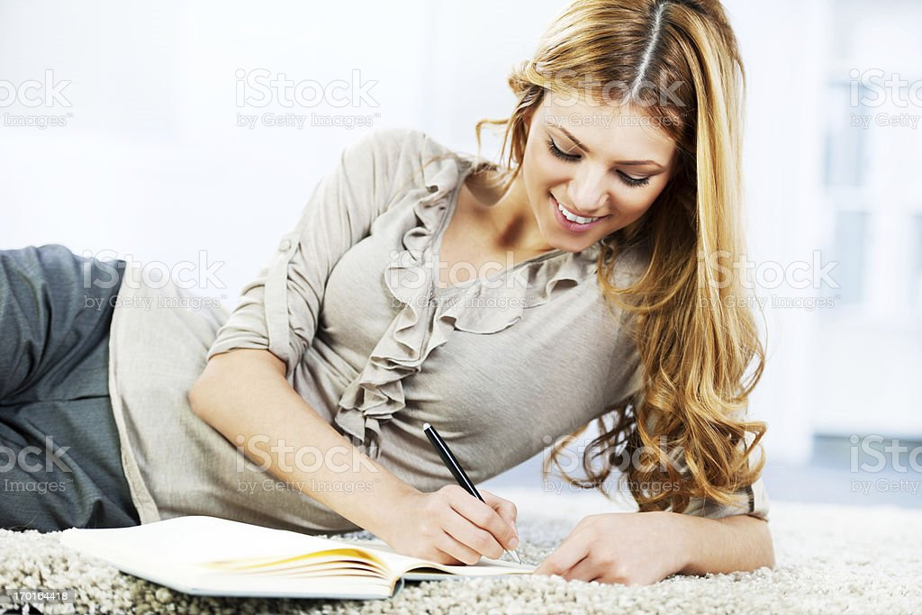 Portrait of a cheerful blonde woman writing diary. royalty-free stock photo