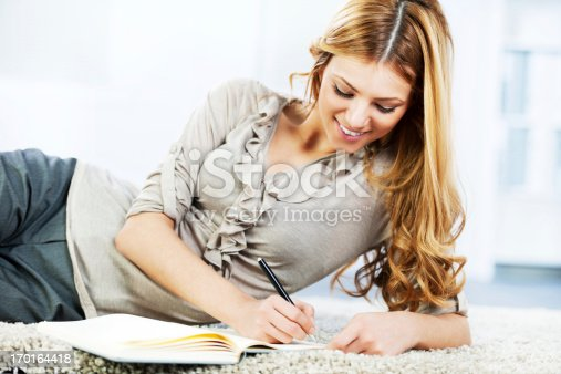 istock Portrait of a cheerful blonde woman writing diary. 170164418