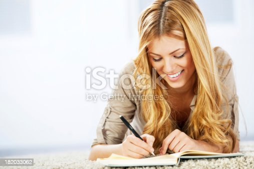 istock Portrait of a cheerful blonde woman writing diary. 182033062