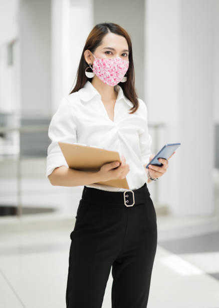 Portrait of a cheerful confident businesswoman in business suit  wears fashion faicial mask to prevent COVID-19, holds document file and cellphone in the business building. Business stock photo stock photo