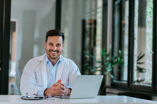 Porträt eines fröhlichen Arztes am Schreibtisch des Arztes. – Foto