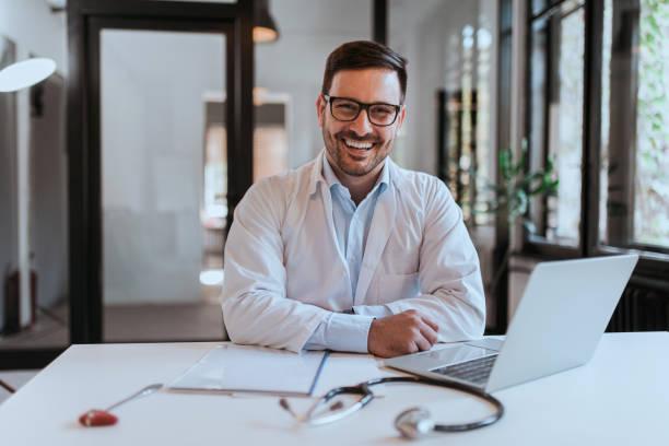 Retrato de un médico alegre en la oficina moderna. - foto de stock