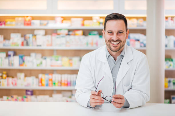 Portrait of a cheerful handsome pharmacist leaning on counter at drugstore. Portrait of a cheerful handsome pharmacist leaning on counter at drugstore. pharmacist stock pictures, royalty-free photos & images