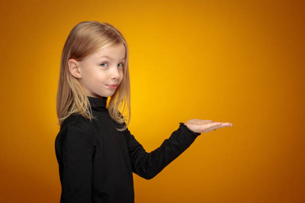 Portrait of a cheerful little blonde girl holding hand palm up looking at the camera stock photo