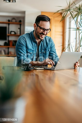 Portrait of a cheerful man using laptop on wooden table, copy space.