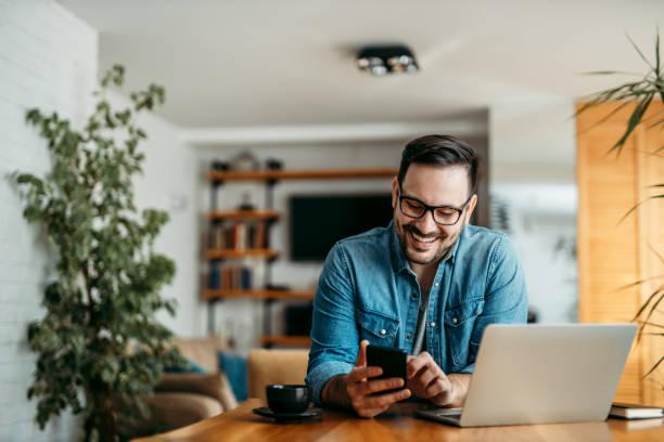 verticale d'un homme gai utilisant le téléphone intelligent au bureau à la maison. - homme photos et images de collection