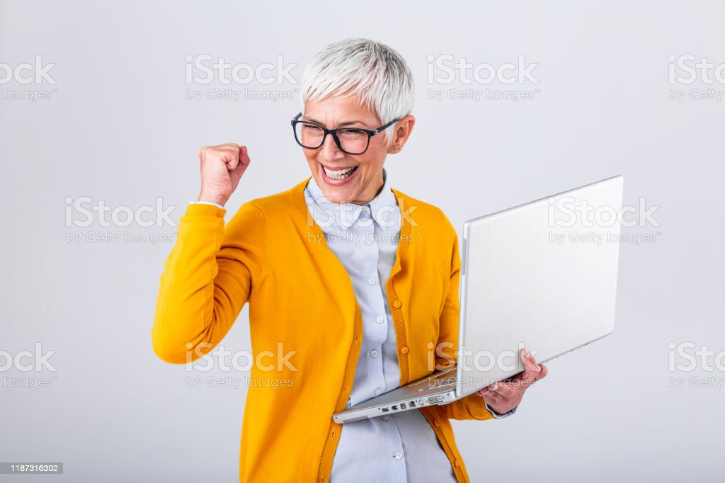 Portrait of a cheerful mature woman with a laptop computer and celebrating success isolated over gray background. Senior lady watching celebrating online bid bet win or great result victory concept Portrait of a cheerful mature woman with a laptop computer and celebrating success isolated over gray background. Senior lady watching celebrating online bid bet win or great result victory concept Achievement Stock Photo