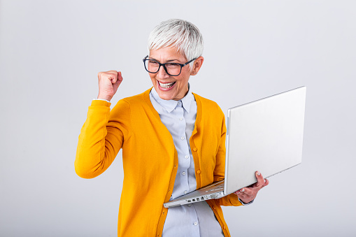 Portrait Of A Cheerful Mature Woman With A Laptop Computer And Celebrating Success Isolated Over Gray Background Senior Lady Watching Celebrating Online Bid Bet Win Or Great Result Victory Concept Stock Photo - Download Image Now