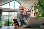 istock Portrait of a cheerful senior businesswoman using smart phone at home office, close-up. 1196485602