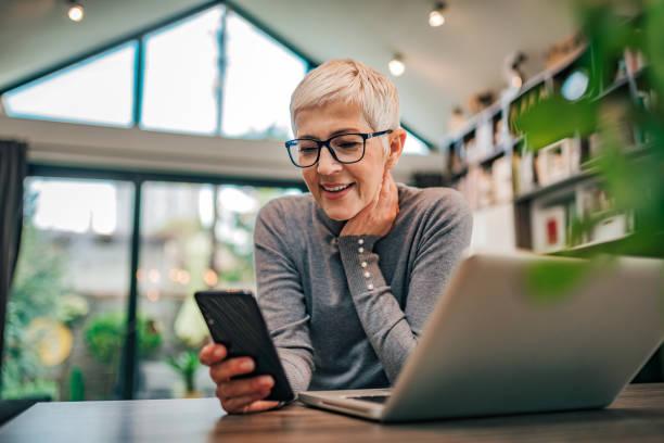 retrato de una alegre mujer de negocios de la tercera edad usando el teléfono inteligente en la oficina en casa, de cerca. - sin personas fotografías e imágenes de stock