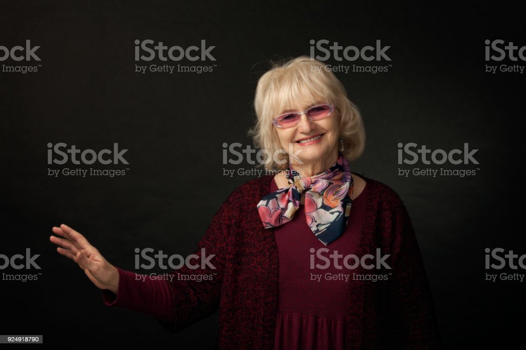 Portrait of a cheerful senior woman in studio stock photo